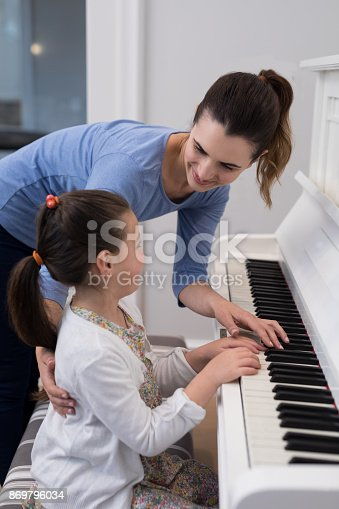 istock Mother assisting daughter in playing piano 869796034