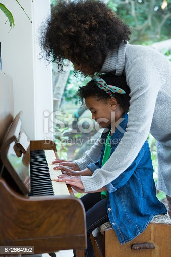 istock Mother assisting daughter in playing piano 872864952