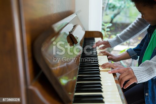 istock Mother assisting daughter in playing piano 872865028