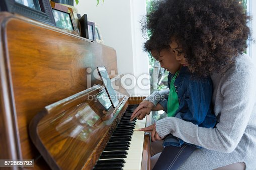 istock Mother assisting daughter in playing piano 872865792