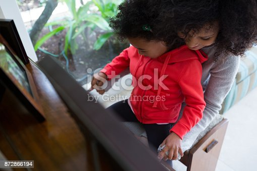 istock Mother assisting daughter in playing piano 872866194