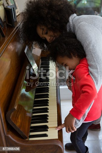istock Mother assisting daughter in playing piano 872866436