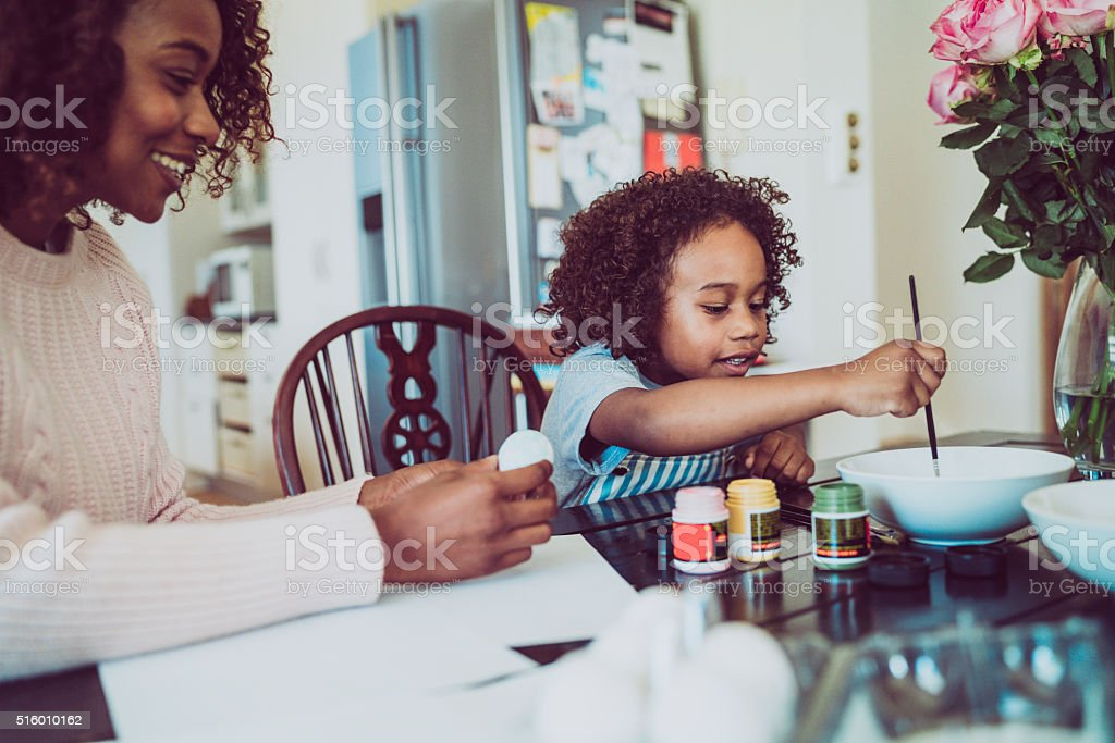 Mother assisting girl in painting Easter egg at home stock photo