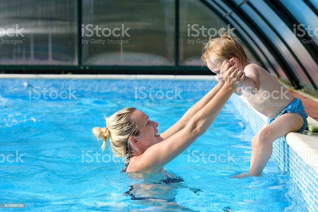 Mother assisting her son in jumping into pool foto royalty-free