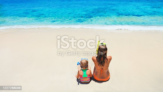 577645320 istock photo Mother, baby girl in snorkeling mask sit on sand beach 1227288058