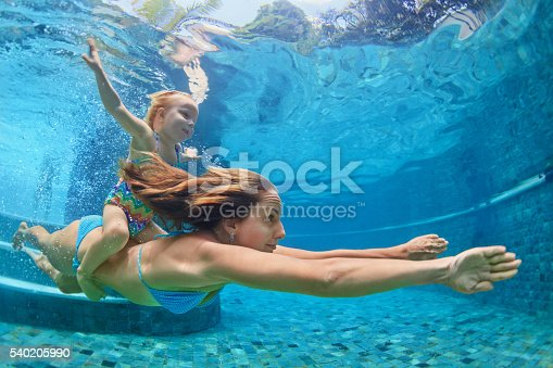 istock Mother, baby girl swim and dive underwater in pool 540205990