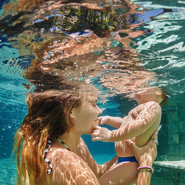 mother, baby swim and dive underwater in swimming pool - lustige babybilder stock-fotos und bilder