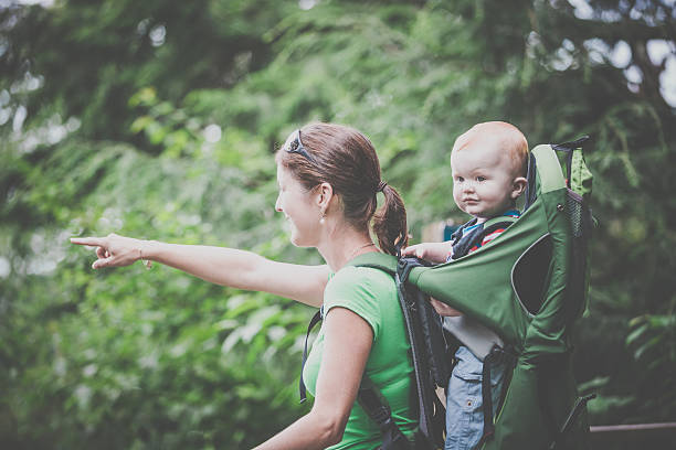 mother backpacking hiking with baby in forest - rückentrage stock-fotos und bilder