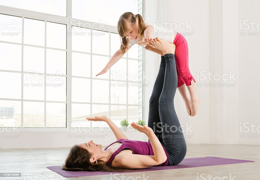 Mother balancing young daughter on her feet while doing yoga stock photo