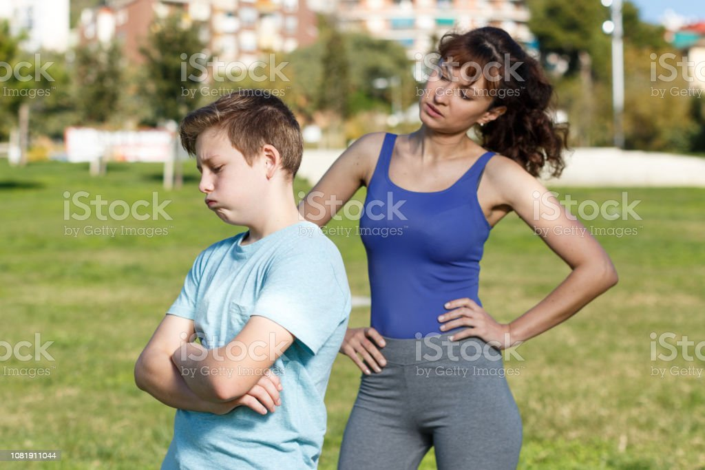 Mother berating son outdoors stock photo