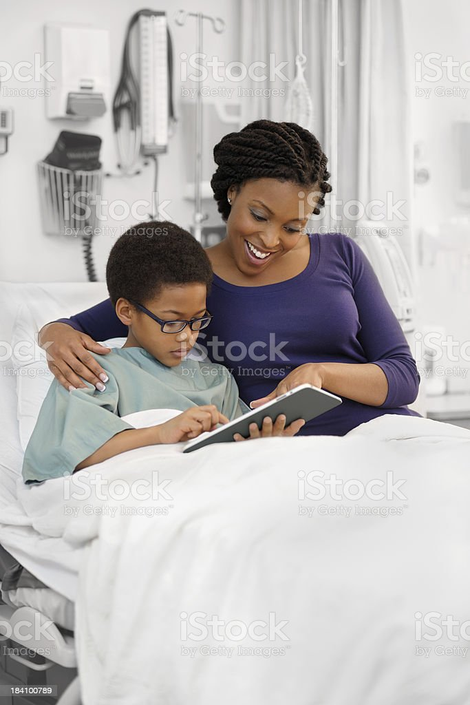 Mother beside boy in hospital bed royalty-free stock photo
