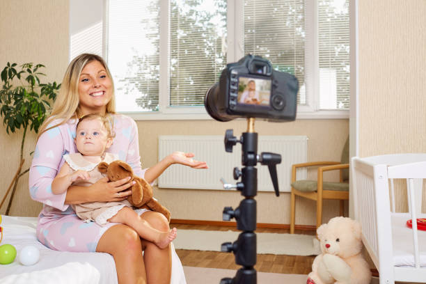 Mother blogger records the video on the camera with the baby in stock photo