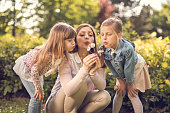Mother blowing at dandelion with daughters in public park
