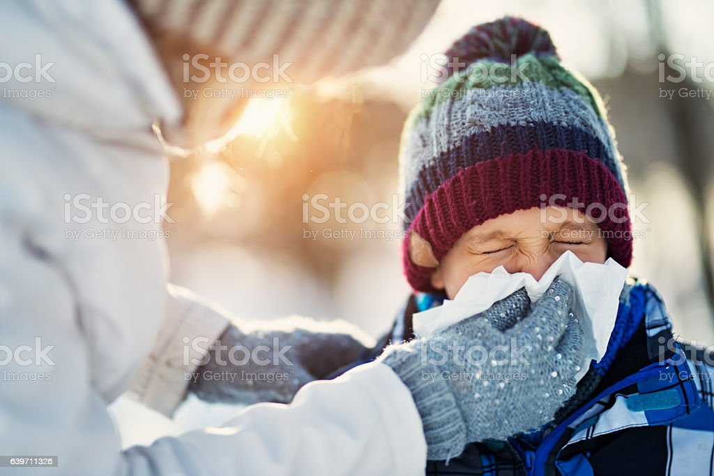 Mother blowing nose of her sick son during winter walk - foto de stock