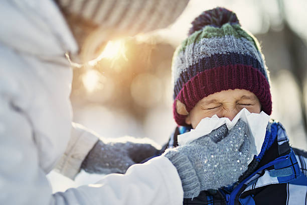 Mother blowing nose of her sick son during winter walk stock photo