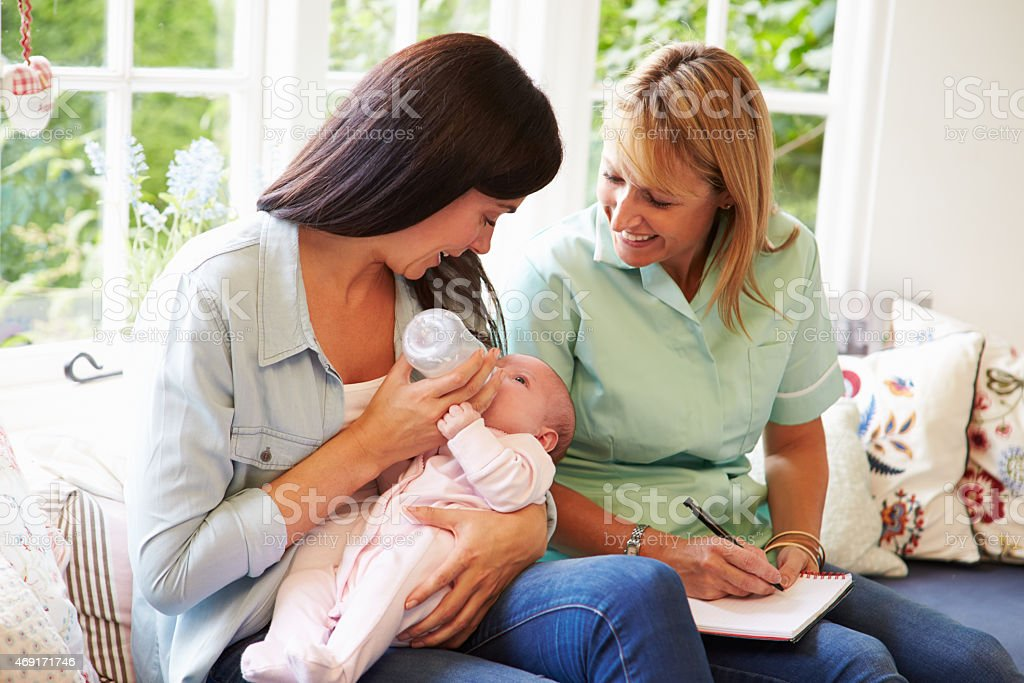 Mother bottle feeding a baby and meeting with health advisor stock photo