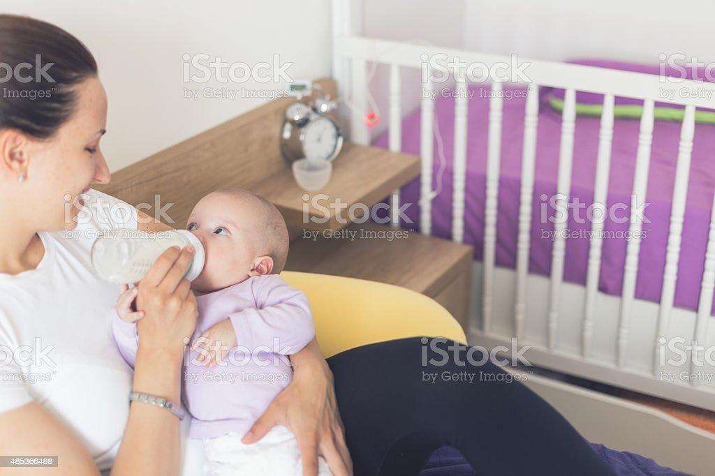 Mother Bottle-Feeding Her Baby stock photo