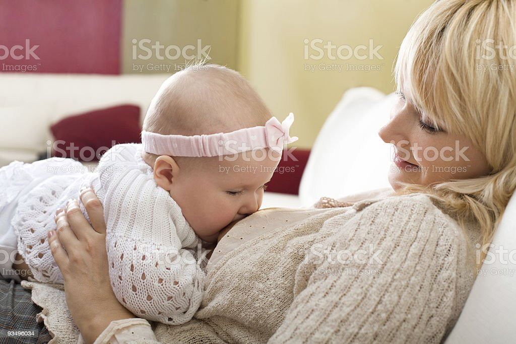 Mother breast feeding her baby girl at home stock photo