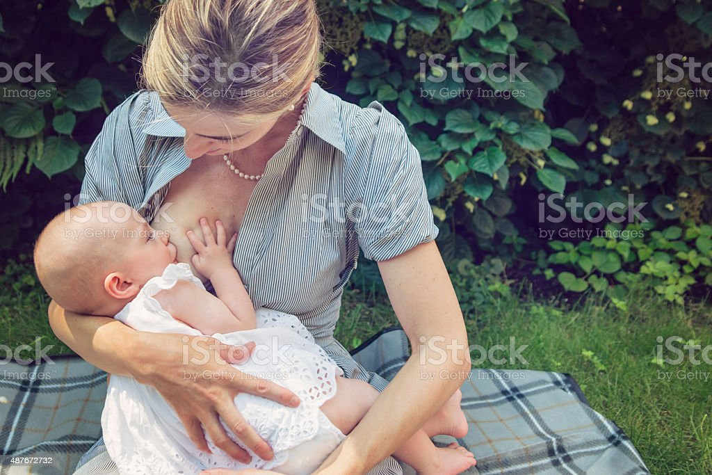 Mother breastfeeding baby girl outdoors in summer nature. stock photo