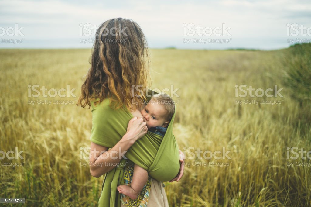 Mother breastfeeding baby in field stock photo