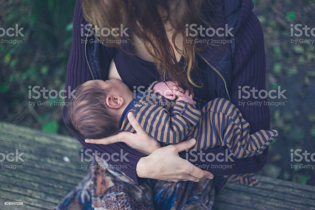 Mother breastfeeding baby in forest - foto de stock