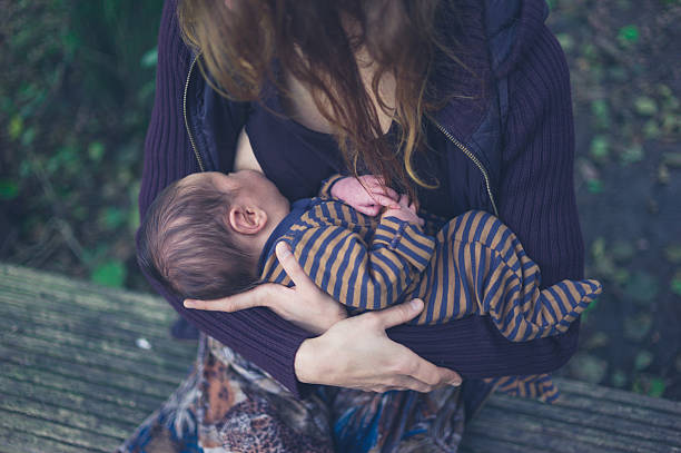 Mother breastfeeding baby in forest stock photo