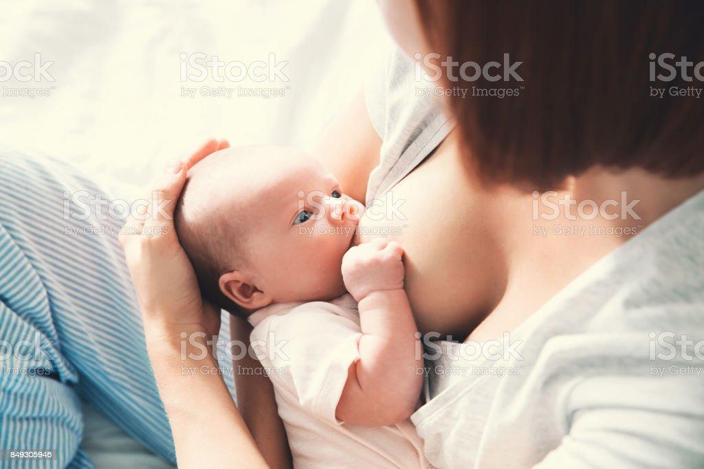 Lactancia materna de la madre al bebé en brazos en casa. - foto de stock