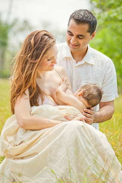 mother breastfeeding baby with husband in romantic outdoors - woman breastfeeding husband stock photos and pictures