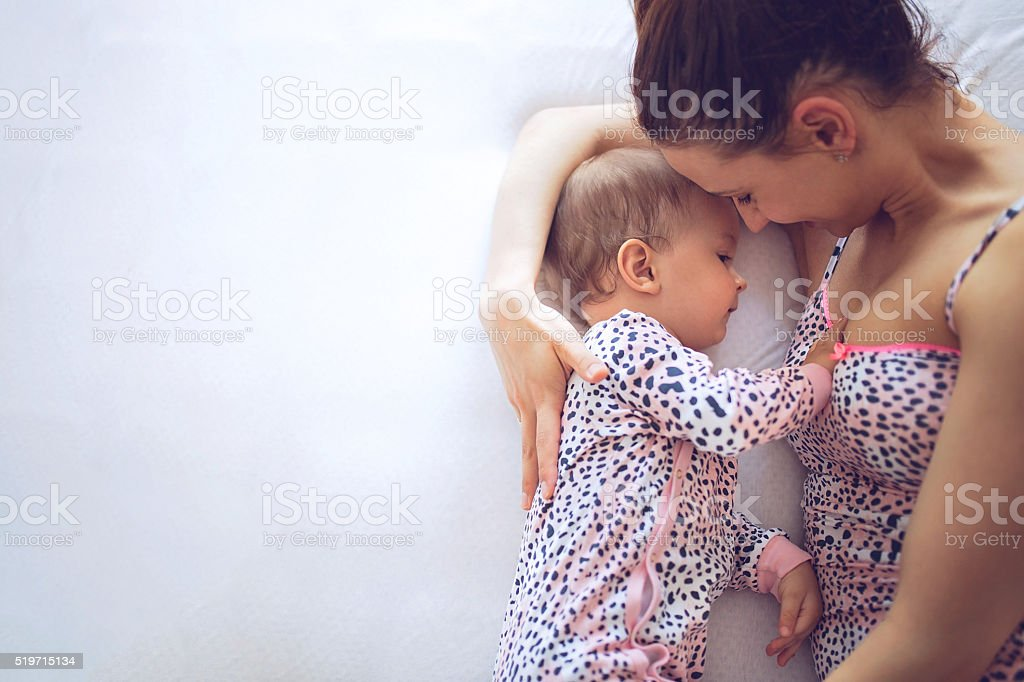 Mother breastfeeding her baby in bedroom stock photo