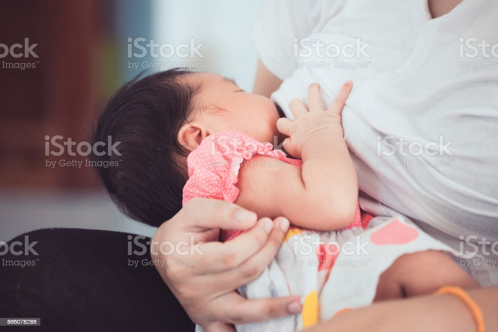 Mother breastfeeding her newborn baby girl. stock photo