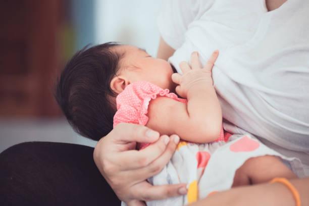 mother breastfeeding her newborn baby girl. - amamentação imagens e fotografias de stock