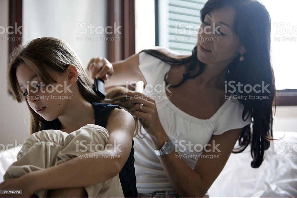 Spazzolare i capelli figlie di madre foto stock royalty-free