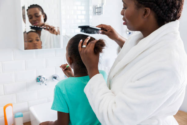 Mother brushing her daughters hair. stock photo