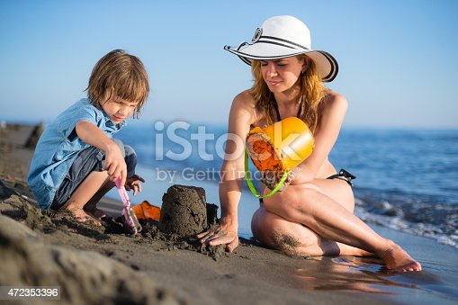 512726470 istock photo Mother building sandcastle with her son 472353396