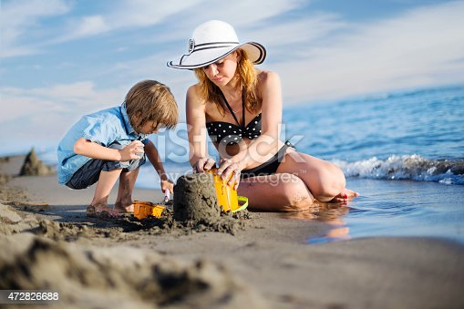512726470 istock photo Mother building sandcastle with her son 472826688