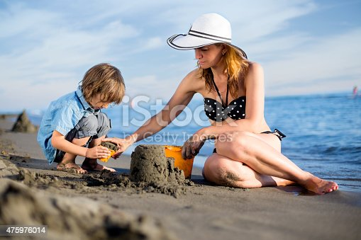 512726470 istock photo Mother building sandcastle with son 475976014