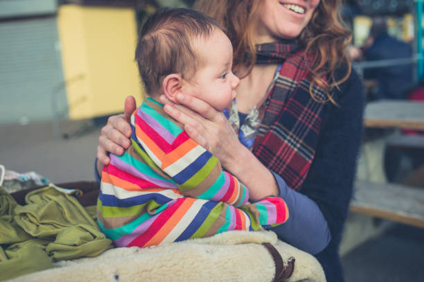 Mother burping baby outside stock photo