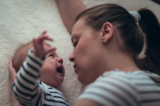 Mother calming her crying baby boy stock photo