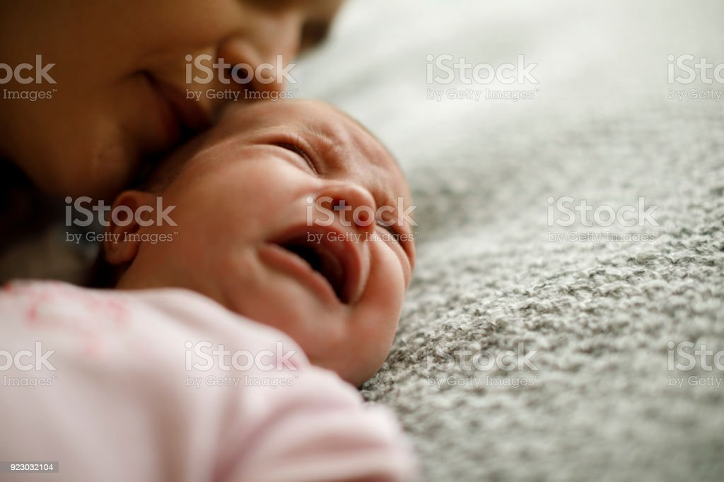 Mother calming her crying baby girl stock photo