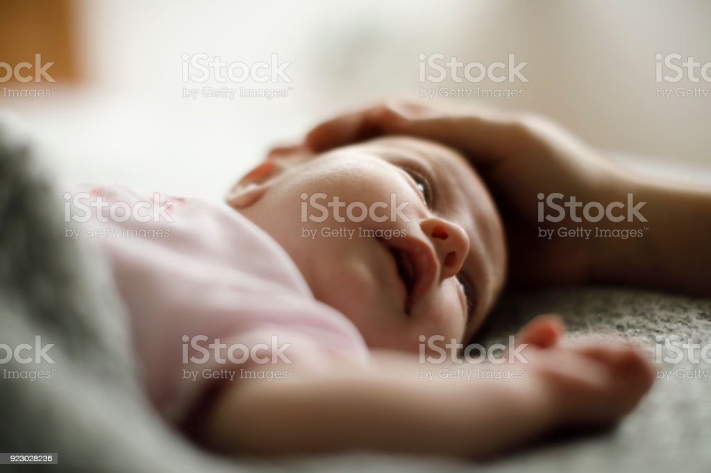 Mother caressing her newborn baby stock photo