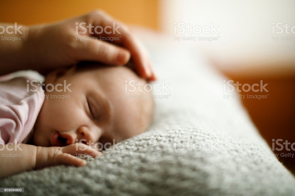 Mother caressing her newborn sleeping baby stock photo
