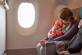 Mother carry her infant baby during flight. Sitting together near the window in airplane