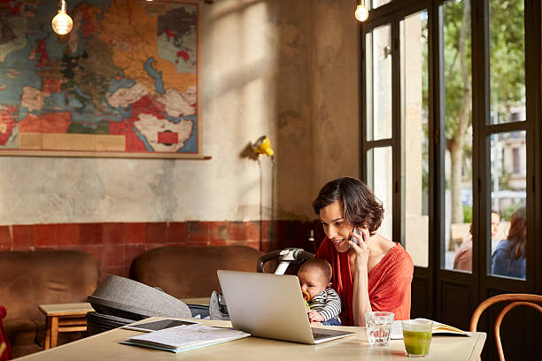 mother carrying baby using technologies at table - femmes actives photos et images de collection