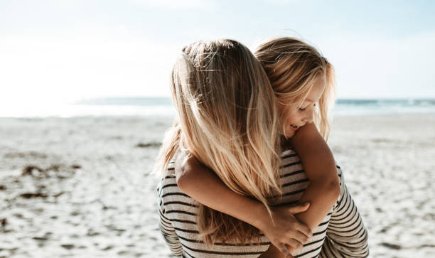 Mother carrying daughter along the beach stock photo