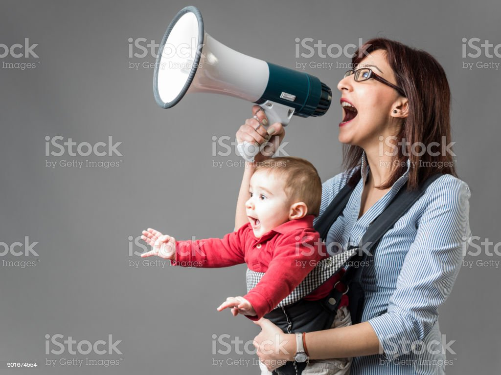 Mother Carrying Her Baby And Shouting Through Megaphone stock photo