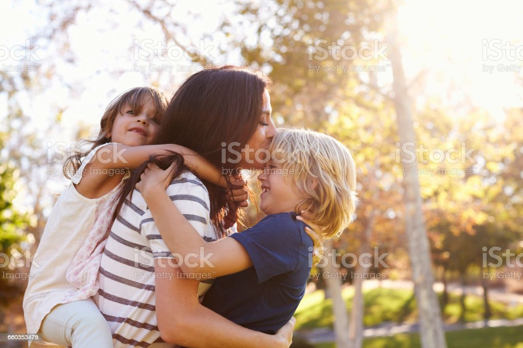 Mother Carrying Son And Daughter As They Play In Park stock photo