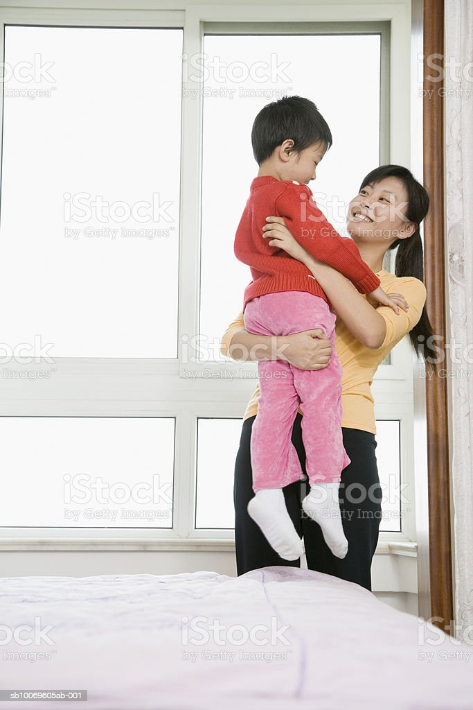 Mother carrying son (4-5) in bedroom 免版稅 stock photo