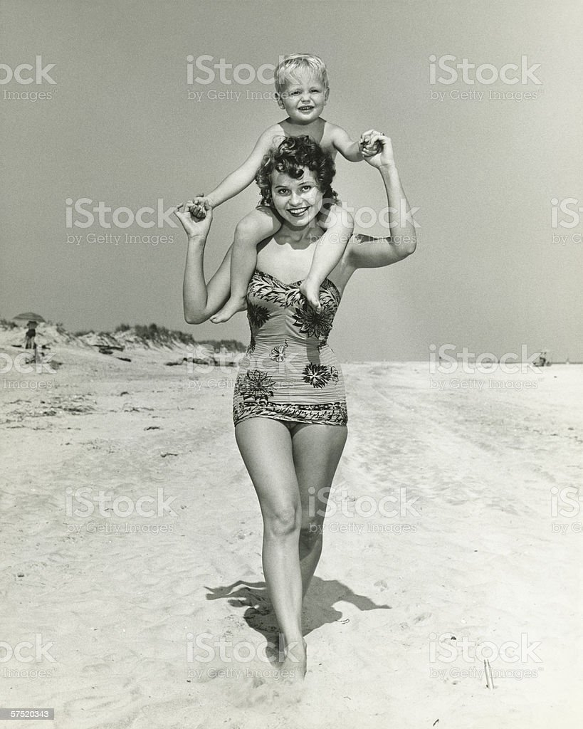 Mother carrying son (2-3) on shoulders, walking on beach, (B&W), portrait stock photo