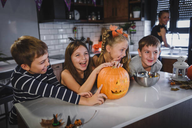 Mother carving Halloween pumpkin with children, making jack-o-lanterns Mother carving Halloween pumpkin with children, making jack-o-lanterns carving craft activity stock pictures, royalty-free photos & images