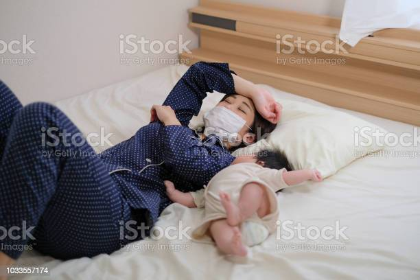 Mother catching a cold is lying on the bed with her baby picture id1033557174?b=1&k=6&m=1033557174&s=612x612&h=nmbpjo7eirhjz1s86s3px ej5cts84cf0y4v 1nabx8=